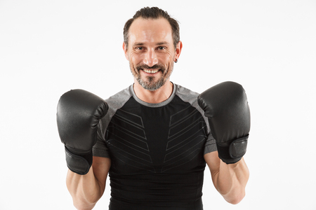 Portrait of a smiling mature sportsman wearing boxing gloves isolated over white background