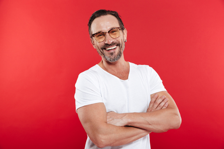 Portrait of an adult happy cheerful man in colorful sunglasses standing isolated over red background looking camera.
