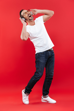 Image of an adult excited man standing isolated over red background listening music with headphones. Stock Photo