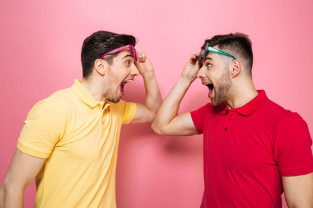 Portrait of a surprised gay male couple in sunglasses looking at each other isolated over pink background