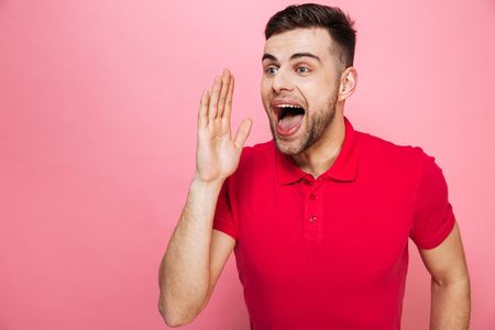 Portrait of a happy young man screaming isolated over pink background