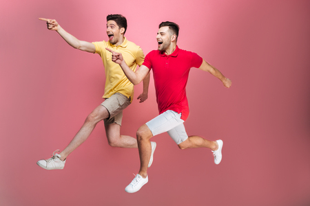 Full length portrait of a happy gay male couple pointing fingers while running isolated over pink background