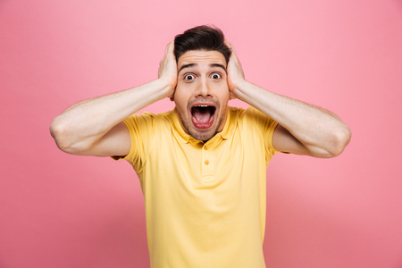 Portrait of a surprised young man looking at camera with open mouth isolated over pink background Standard-Bild