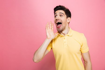 Portrait of a happy young man screaming loud isolated over pink background Reklamní fotografie