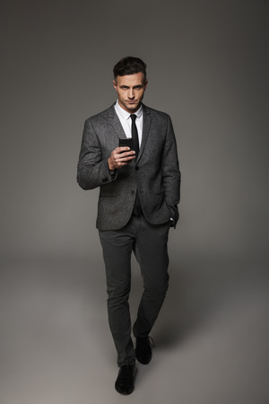 Full-length photo of serious business man wearing businesslike suit and tie looking strictly on camera with smartphone in hand isolated over gray background