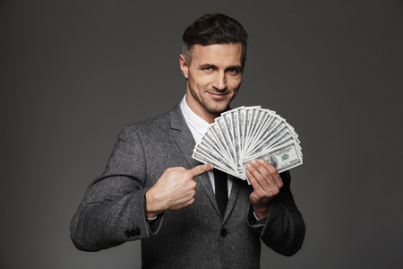 Photo of happy man 30s in formal costume demonstrating lots of money dollar banknotes and pointing finger on bills isolated over gray background Stock Photo
