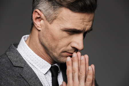 Photo closeup of thoughtful calm man wearing classic costume and tie keeping palms together in praying pose isolated over gray background Stock Photo