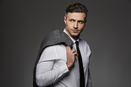 Photo of successful businessman 30s in formal wear looking aside on copyspace and holding jacket over his shoulder isolated over gray background