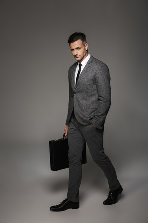 Full length portrait of male office worker dressed in businesslike costume posing on camera with briefcase in hand isolated over gray background