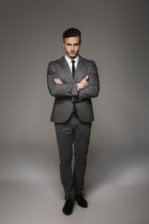 Full length portrait of masculine man wearing business suit posing on camera with serious look keeping arms folded isolated over gray background Stock fotó
