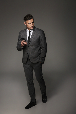 Full-length image of confident business man wearing suit and tie looking aside while holding cell phone isolated over gray background