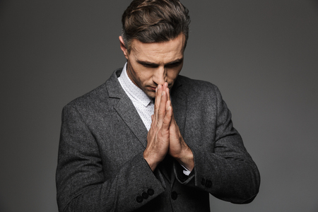 Photo of elegant concentrated man wearing classic costume holding palms together for praying isolated over gray background