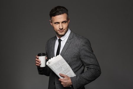 Image of confident brunette man dressed in business costume looking aside with takeaway coffee and newspaper in hands isolated over gray background