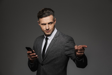 Image of adult man with severe look in business costume holding mobile phone and pointing finger on copyspace isolated over gray background
