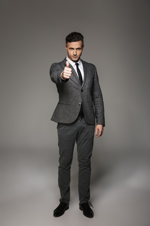 Full length portrait of caucasian businessman wearing business suit posing on camera and showing thumb up isolated over gray background Stock fotó
