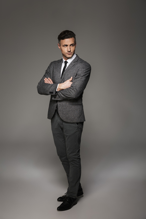 Full length portrait of fashionable man wearing business suit looking aside with focused gaze keeping arms crossed isolated over gray background