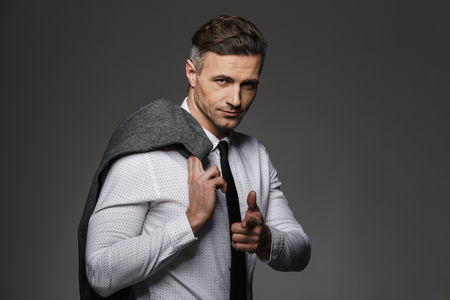 Photo of fashionable man wearing business suit gesturing finger on you while holding jacket over his shoulder isolated over gray background Stock fotó