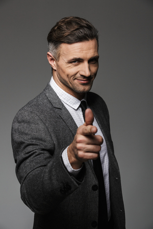 Portrait of joyful business man wearing business suit posing on camera and pointing finger on you isolated over gray background