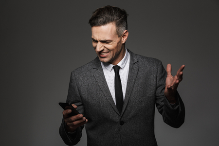 Photo of businesslike man wearing business costume expressing outrage and resentment while using mobile phone in office isolated over gray background Stock fotó