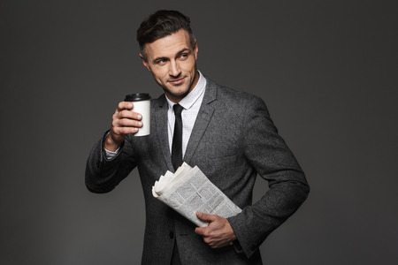 Image of busy businesslike man dressed in business costume looking aside and drinking takeaway coffee with newspaper in hand isolated over gray background