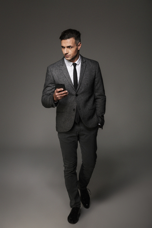 Full-length image of young unshaved man 30s wearing suit and tie looking aside while holding mobile phone isolated over gray background