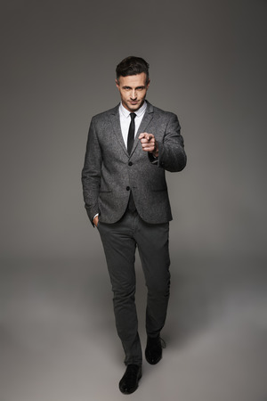 Full length portrait of stylish entrepreneur man wearing businesslike costume posing on camera and pointing finger on you isolated over gray background