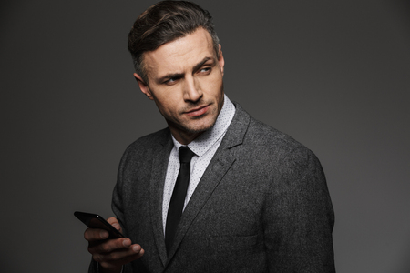 Image of young unshaved man dressed in business costume chatting or working on mobile phone and looking aside isolated over gray background