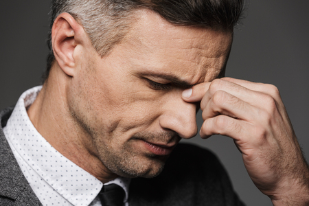 Portrait closeup of exhausted caucasian man in formal wear closing eyes and touching his nose bridge isolated over gray background