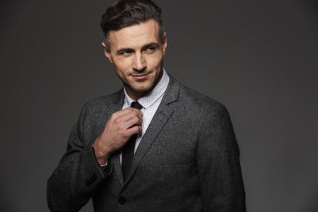 Afbeelding van volwassen ongeschoren man met pak opzij kijken terwijl het corrigeren van zijn zwarte stropdas geïsoleerd over grijze achtergrond