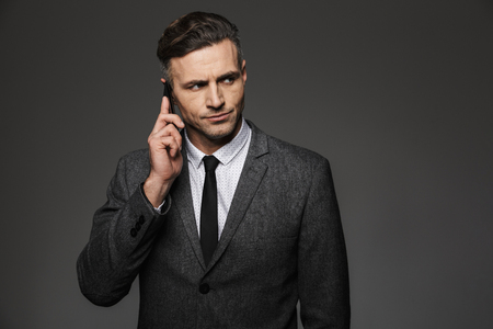 Photo of masculine man 30s dressed in businesslike costume working in office and talking on phone about business isolated over gray background