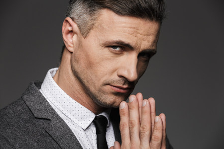 Photo closeup of stylish serious man wearing white shirt and tie keeping palms together in praying pose isolated over gray background