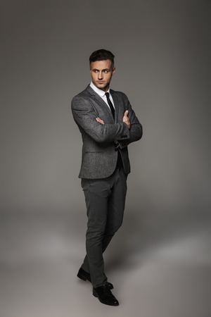 Full length photo of handsome man wearing business suit looking on camera with meaningful gaze keeping arms crossed isolated over gray background