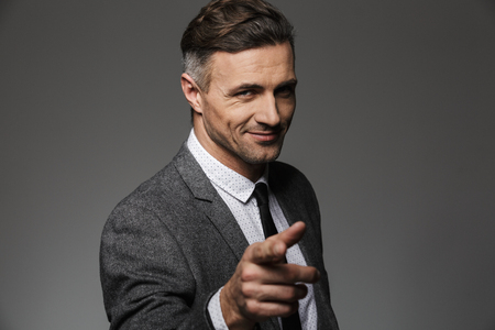 Horizontal portrait of caucasian happy businessman wearing business suit posing on camera and pointing finger on you isolated over gray background Stock fotó