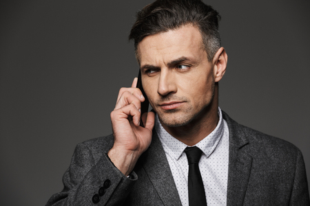 Photo closeup of beautiful man 30s dressed in businesslike costume working in office and talking on phone about business isolated over gray background Stock fotó