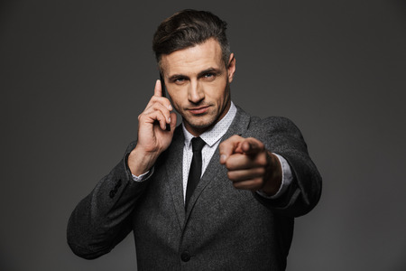 Image of serious man employer dressed in business costume having mobile talk in office and pointing finger on you isolated over gray background