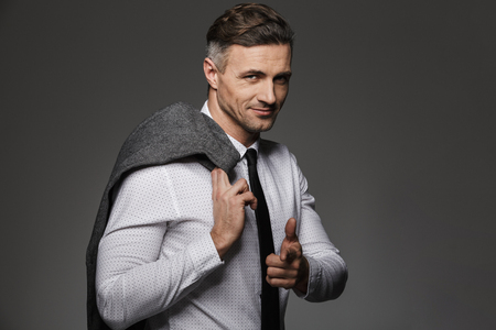 Photo of handsome man wearing business suit pointing finger on camera and holding jacket over his shoulder isolated over gray background