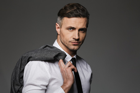 Image of mature unshaved man wearing business suit looking on camera and holding jacket over his shoulder isolated over gray background Stock fotó