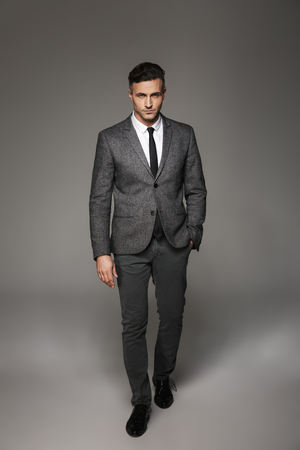 Full length portrait of successful businessman wearing business suit posing on camera with serious look and hand in pocket isolated over gray background