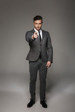 Full length portrait of caucasian businessman wearing business suit posing on camera and pointing finger on you isolated over gray background