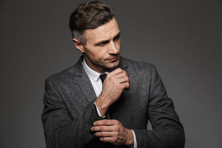 Fashion image of masculine man dressed in business suit looking aside, while fasten cufflink or button on sleeve of jacket isolated over gray background Standard-Bild