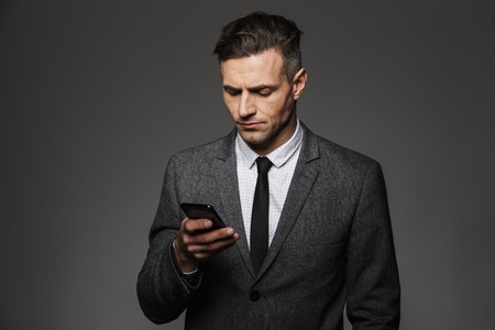 Image of young unshaved man dressed in business costume chatting or working on mobile phone isolated over gray background