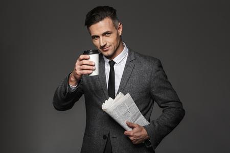 Photo of handsome businesslike man dressed in business costume drinking takeaway coffee in office and reading newspaper isolated over gray background