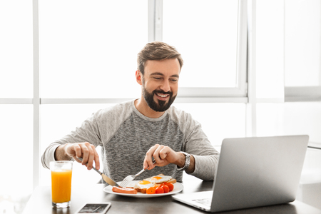 Unshaved satisfied man 30s wearing casual clothing eating fried eggs for breakfast and looking at notebook