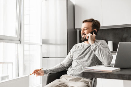 Image of businesslike man 30s wearing casual clothing working on laptop while looking out window and speaking on cell phone at home