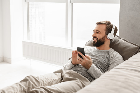 Handsome man with european appearance in basic clothing lying on couch in house and listening to music using black cell phone wearing wireless headphones Stock Photo