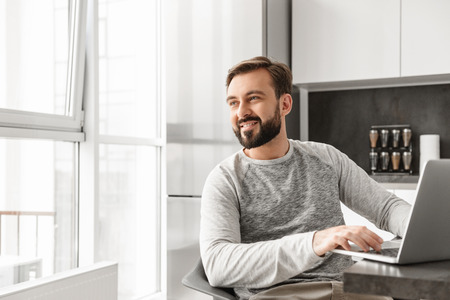 Picture of joyous man 30s in casual shirt working on laptop at home and looking out window