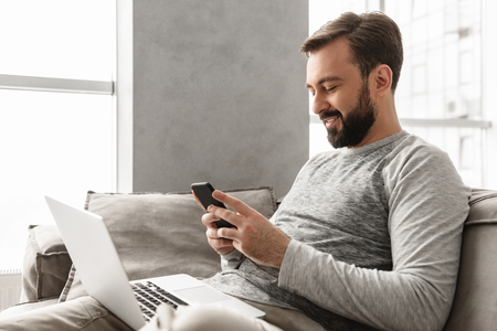 Image of caucasian man 30s in casual wear sitting on sofa in living room while using smartphone and laptop
