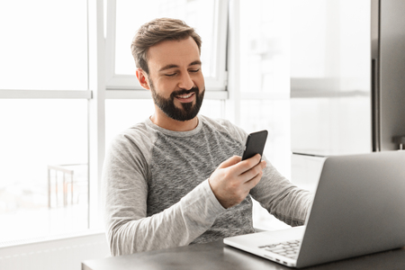 Image of caucasian man 30s wearing casual clothing working on laptop while sitting at table near window indoor and holding mobile phone