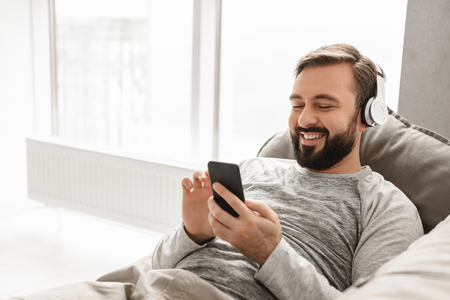 Positiver Mann 30s in der Grundkleidung, die auf Sofa im Haus liegt und Musik unter Verwendung des schwarzen Handys mit drahtlosen Kopfhörern hört