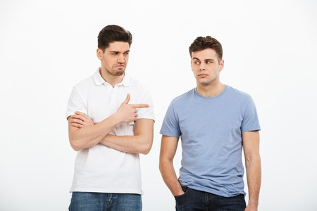 Portrait of two disappointed young men pointing finger isolated over white background Reklamní fotografie